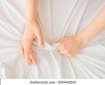 Hand clutches or grasps a white crumpled bed sheet in a hotel room, a sign of ecstasy, feeling of pleasure or orgasm. Orgasm is the greatest point of sexual pleasure or a climax of sexual excitement