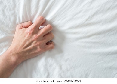 Hand clutches / grasps a white crumpled bed sheet in a hotel room, a sign of ecstasy, feeling of pleasure or orgasm. Orgasm is the greatest point of sexual pleasure or a climax of sexual excitement.
