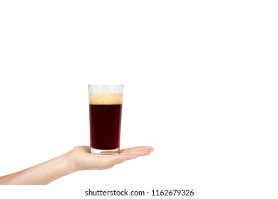 Hand with cold glass of dark beer or kvass with foam isolated on white background, copy space template