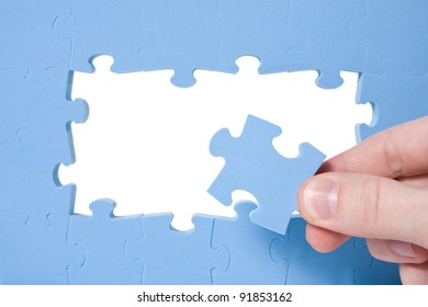 Hand collecting a part of a blue puzzle