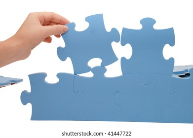 Hand collecting a part of a puzzle