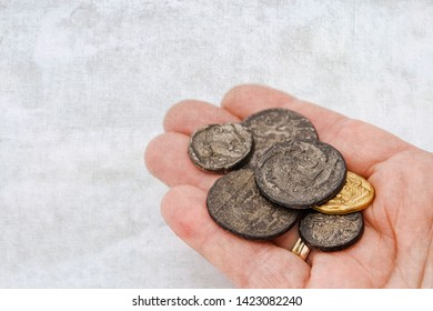 hand with a collection of old roman coins