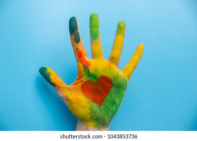 hand in colorful paint with red heart