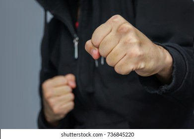 hand to hand combat. Street fist-fighter. Male fist closeup. fighter in a black hoodie prepares to strike with his fist.