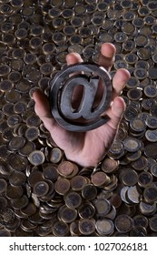 Hand coming out of a pile of coins, holding the at sign of internet