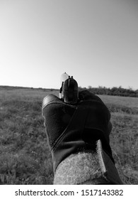 Hand commando in a protective glove holds a gun. Aiming for shooting. Black and white monochrome shot.