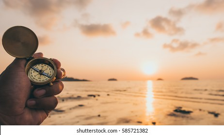 Hand with compass at the beach