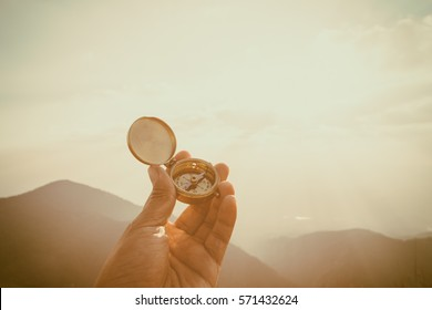Hand with compass at mountain road at sunset sky, Monjong Chiang Mai Thailand
