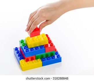 Hand completing colorful plastic brick structure on white background