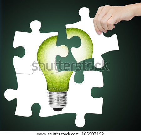 hand completing jigsaw puzzle of  green energy light bulb, sign of environment saving