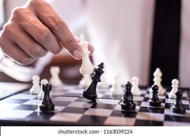 Hand of confident businessman use king chess piece white playing chess game to crash overthrow the opposite team and development analysis new strategy plan, business strategy for win and success.