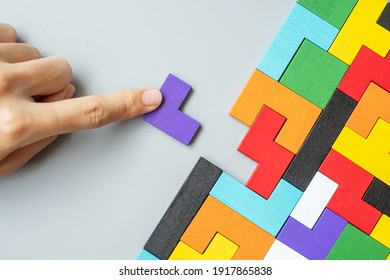hand connecting geometric shape block with colorful wood puzzle pieces. logical thinking, business logic, Conundrum, decision, solutions, rational, mission, success, goals and strategy concepts