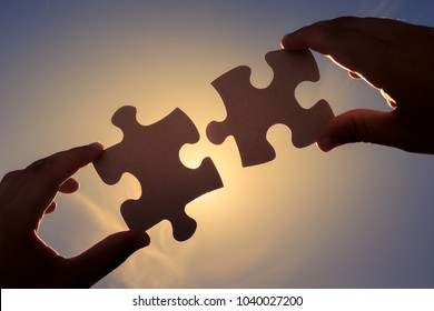 Hand connecting puzzle pieces together.