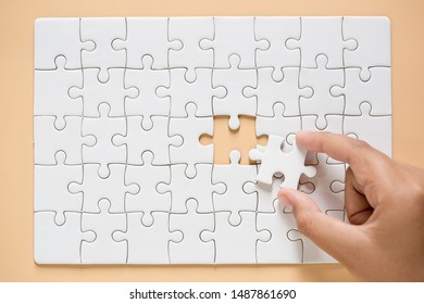 hand connecting two puzzle pieces on table background, business strategy concept