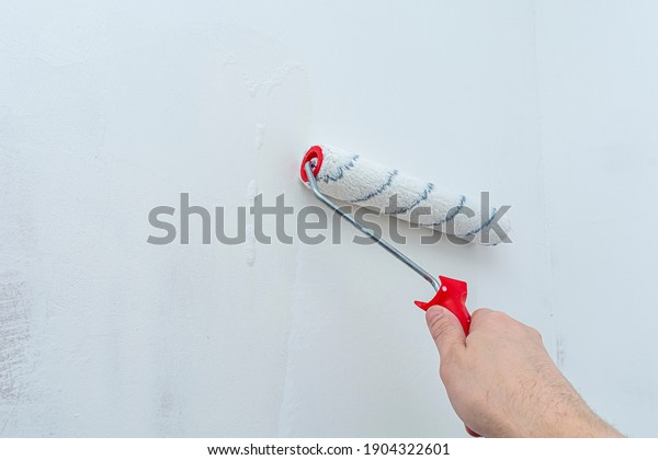 Hand with a construction roller in the process of priming the wall. The concept of renovation and decoration of the room. Antiseptic treatment. Preparing the wall for painting or wallpapering.