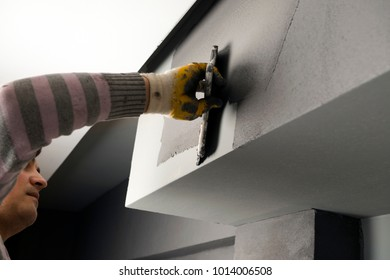 Hand of a construction worker plastering and smoothing concrete wall