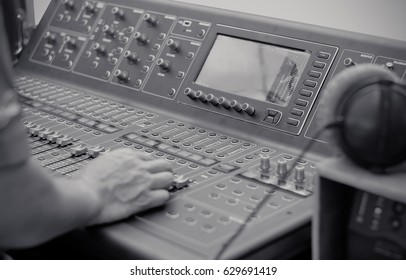 Hand Control of high-quality audio and equalizer volume on sound mixing console with headphones ,selective focus, black and white tone