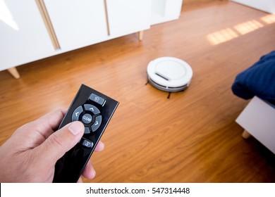 Hand controlling romote of robotic vacuum on wood laminate floor.
