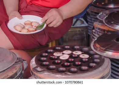 Woman's hand cooking Coconut Rice Cake,Thai coconut pudding (Thai traditional dessert, Kanom Krok, Dessert of Thai traditional sweetmeat or Thai Pancake, Delicious street food in Thailand.