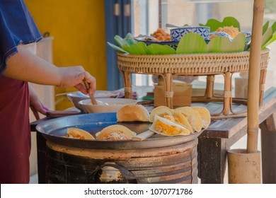 "Woman's hand cooking Thai crispy pancakes (Thai traditional dessert call ""Kanom Bueang""), Delicious street food in Thailand."