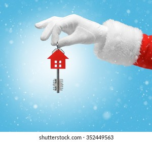Hand in costume Santa Claus is holding house keys / studio shot of man's hand holding keys / Merry Christmas & New Year's Eve concept / Closeup on blurred blue background.