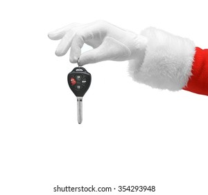 Hand in costume Santa Claus is holding car keys / studio shot of man's hand holding keys / Merry Christmas & New Year's Eve concept / Closeup isolated on white background