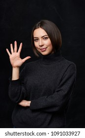 Hand counting - five fingers.Smiling woman in grey turtleneck sweater over dark background showing five fingers