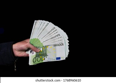 Hand counting holding and showing euro money or giving money. World money concept, 100 EURO banknotes EUR currency isolated on black with copy space. Concept of rich people, saving or spending money