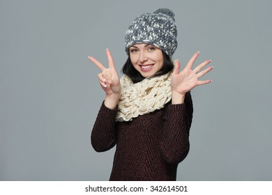 Hand counting - seven fingers. Portrait of woman on grey background wearing woolen hat and muffler showing seven fingers