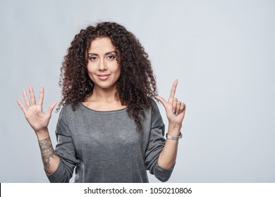 Hand counting - seven fingers. Smiling woman showing seven fingers