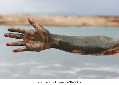 Hand covered with mud from Dead sea, Jordan. Skincare treatment