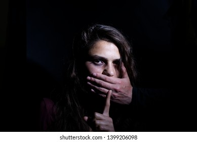 the man's hand covering the woman's mouth shows silence about domestic violence against girls against a dark background. Domestic violence concept