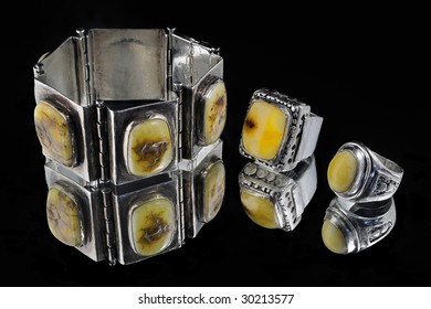 Hand crafted amber & silver bracelet on black background