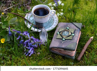 Hand crafted diary book with flowers, crystal and tea cup in the garden. Esoteric, gothic and occult background with magic objects, mystic and fairy tale concept outdoors.