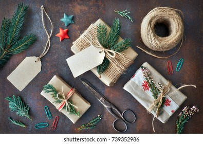 Hand crafted gifts on dark background with Christmas decorations. Seasonal background shot from above. Flat lay, top view, filtered image. Tag mockup, copy space on the tags.