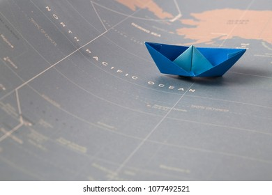 Hand crafted paper boat on worldmap background
