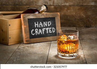 Hand crafted small batch craft liquor glass bourbon whisky scotch brandy rum on wooden rustic surface whiskey