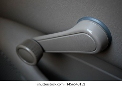 Hand crank, non-electric, manual car window knob in a dove grey color an old vehicle. Changing automobile technology concept.