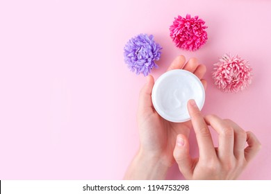 Hand cream and flowers on a pink background. Skin and hand care. Moisturizing and eliminating the dryness of the hands skin. Copy space