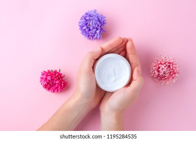 Hand cream and flowers on a pink background. Skin and hand care. Moisturizing and eliminating the dryness of the hands skin
