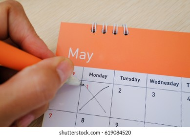 Hand cross on calendar. 1st of May is Labour day and an international public holiday.