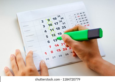 Hand crosses off the green marker days in the calendar. White calendar. Weekends are highlighted in red. Close up