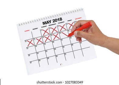 Hand crossing out days up to the 10th on May 2018 Calendar using red marker white background