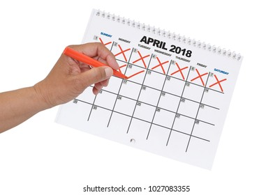 Hand crossing out days up to the 10th on April 2018 Calendar  with orange marker white background