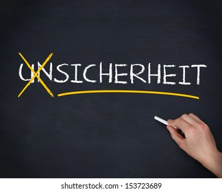 Hand crossing out the german word unsicherheit on a blackboard
