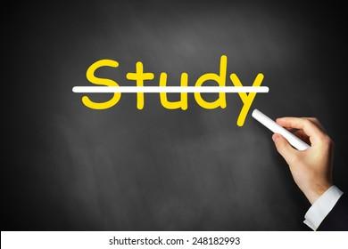 hand crossing out study written on black chalkboard