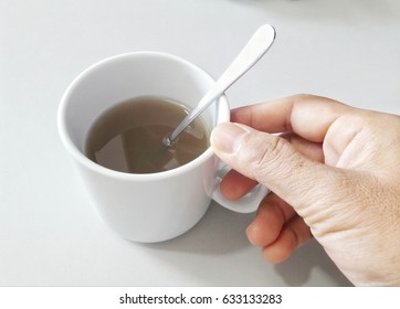 Hand with a cup of ginger ready to drink