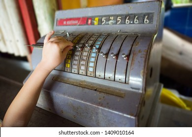 Hand of a curious child playing and pressing buttons on a collectible and antique style cash register