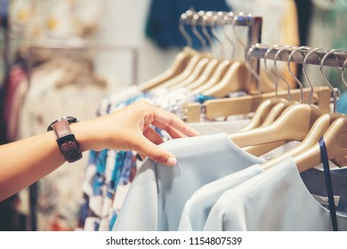 hand of customer choosing clothes in a clothing store