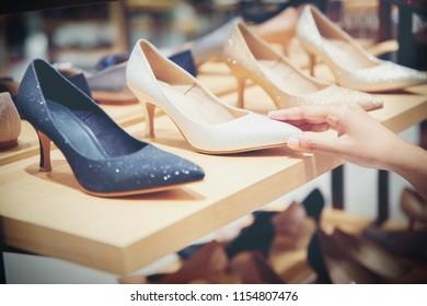 hand of customer choosing shoes in luxury store